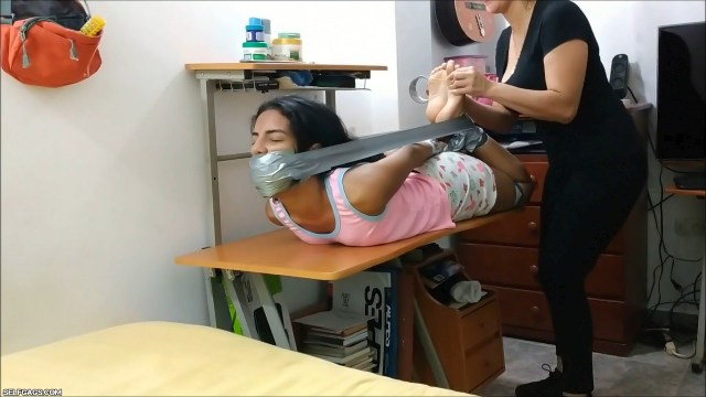 sexy latina babysitter gagged and hogtied barefoot with duct tape on table by milf