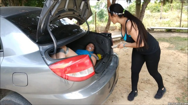 Bound and gagged damsel in distress stuck inside car trunk