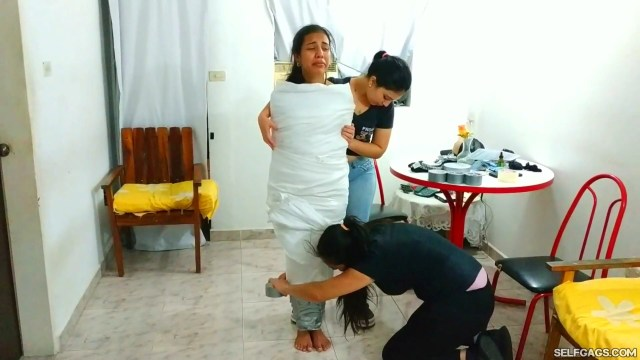 Young latina girl covered in sheets and wrapped up in duct tape mummification bondage