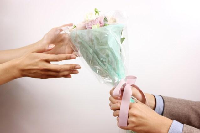 フリー写真 花束のプレゼントとカップルの手
