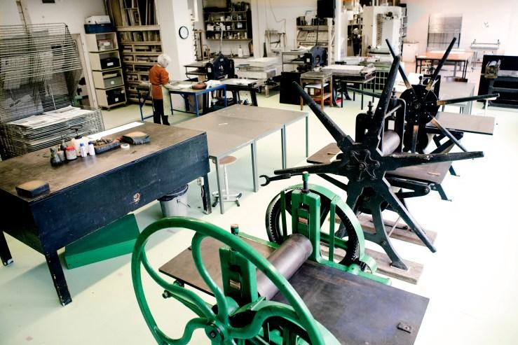 Foto van de diepdruk studio met 3 etspersen en werktafels. Daarachter lithografie en zeefdrukruimte.