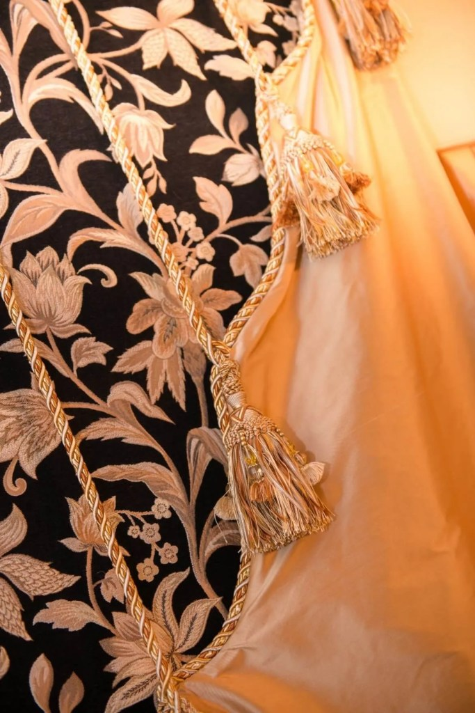 A close up shows the details of the drapery panel that's pulled by rope trim.
