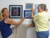 Lynette and Linda hanging a wall.