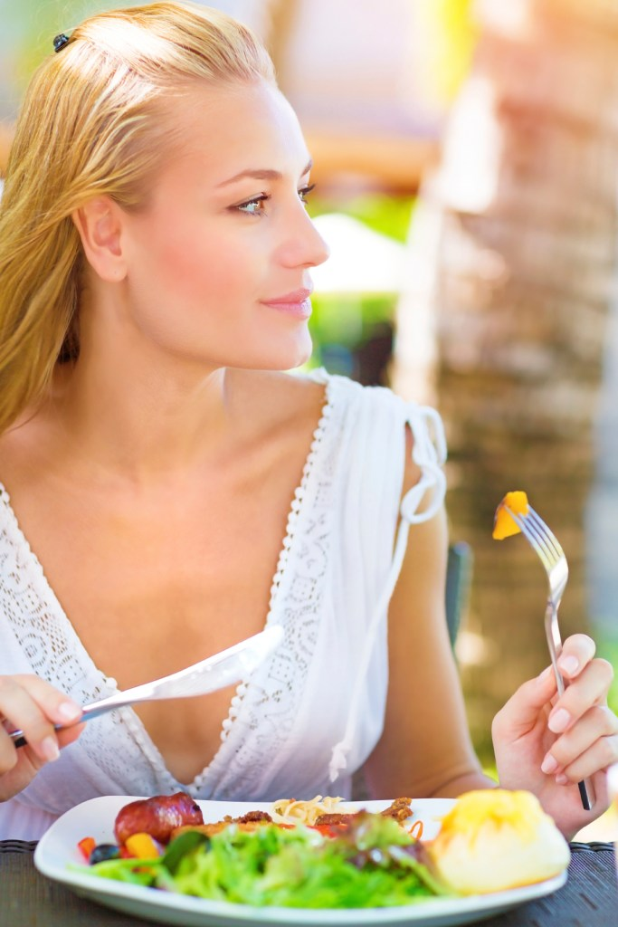 Closeup portrait cute blond girl sitting in outdoors restaurant and having breakfast, eating fresh vegetables salad, luxury healthy eating concept