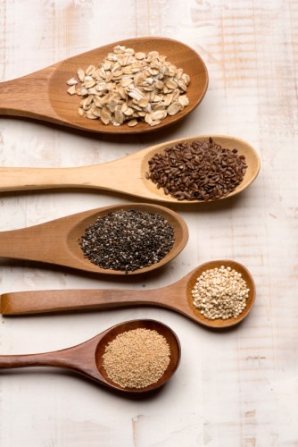 Healthy cereal spoons, from top to botton: oat, linseed, chia, quinoa, and amaranth seeds.