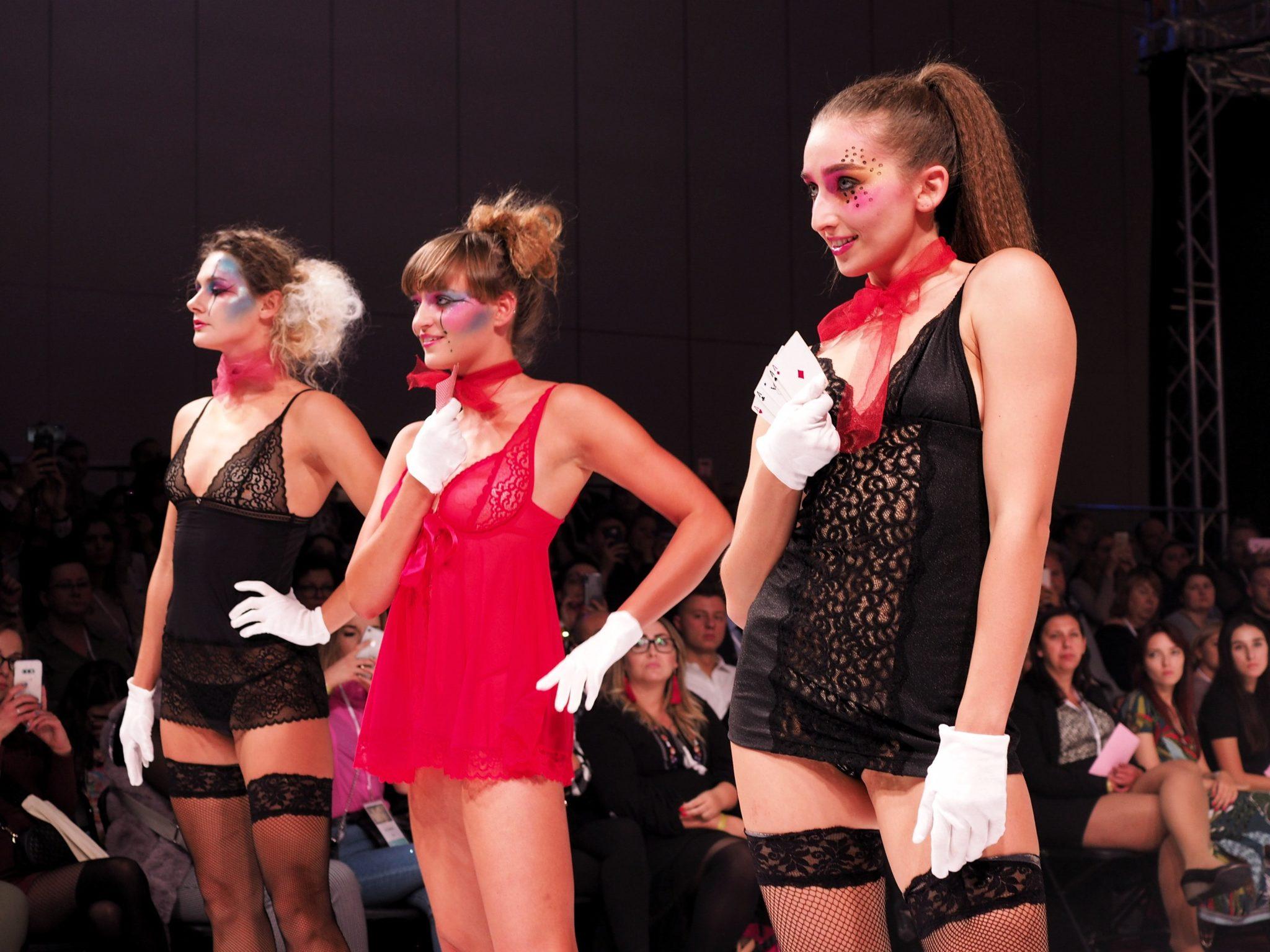 trzy szczupłe modelki pozują w koszulkach nocnych z czerwonymi chusteczkami na szyi, w białych rekawiczkach i z taliami kart w rękach