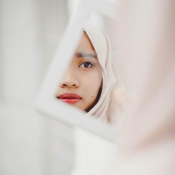 Głównym punketm zdjęcia jest twarz młodej kobiety odbijająca się w trzymanym przez nią lustrze. Dziewczyna ma na sobie jasnoróżowy niqab, patrzy w lustro z napięciem
