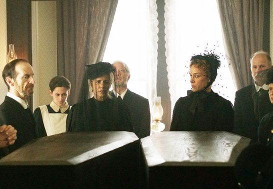 Lizzie and sister look over caskets at funeral