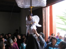 Some church goers were more interested in fixing a statues head-dress more then the baby swinging behind them.