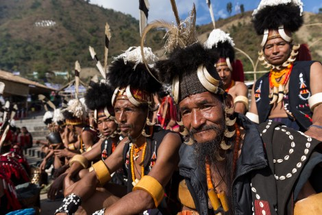 Chang tribesmen waiting to perform at Hornbill Festival 2015, Kisama Village, Kohima District, Nagaland, India. Naga heritage is celebrated during colourful festivals: Hornbill is the Nagaland state government's ten-day festival organised every December, when Naga tribes converge wearing their traditional costumes and finery for tourists.