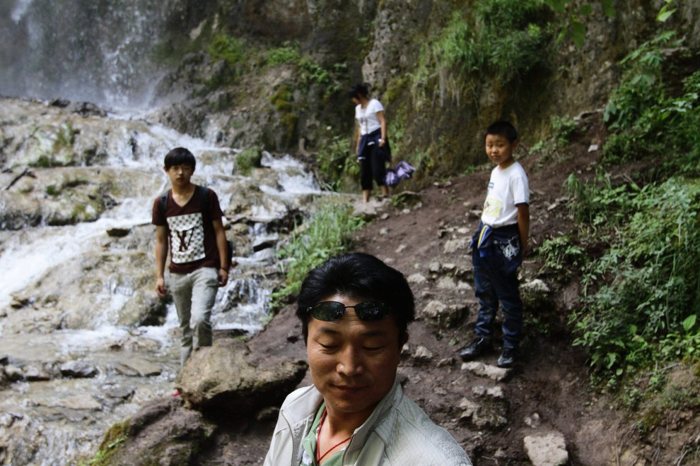 Tourists exploring a waterfall in the Jiuzhaigou National Park.