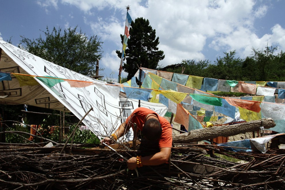 A Tibetan man adjusts prayer flags outside his home near the Jiuzhaigou National Park.
