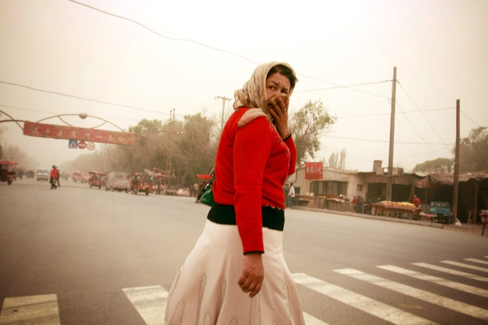 A woman protects herself from the airborne sand which has descended on the town of Minfeng in Xinjiang province. The town's proximity to the Taklamakan desrt means it is regularly bombarded by sandstorms.