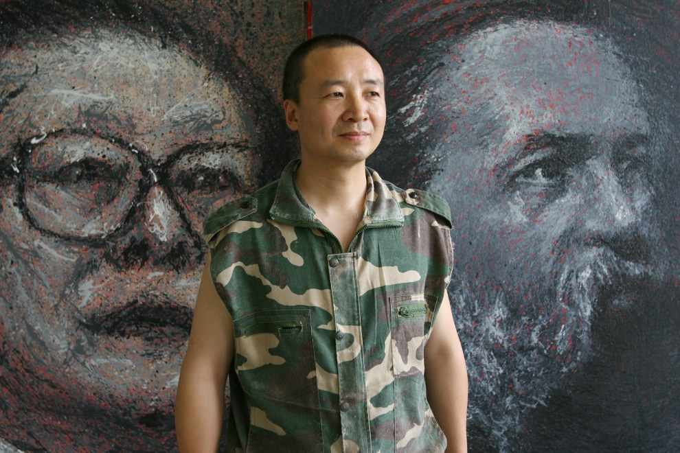 An artist stands in front of his paintings in his studio in the Songzhuang art district.