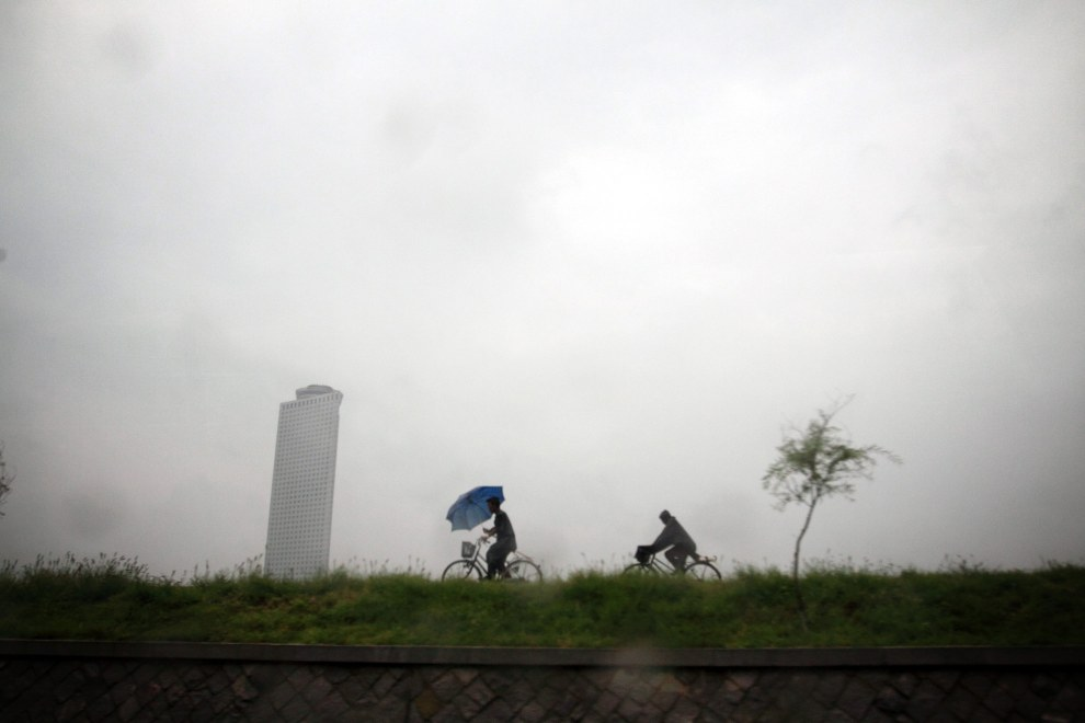 North Koreans cycle during a rainshower near the Yanggakdo Hotel, in central Pyongyang.
