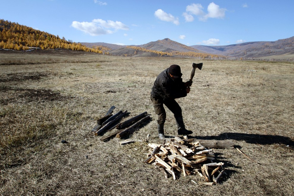 A Mongolian man cutting up firewood near the Altansumber Forest.
