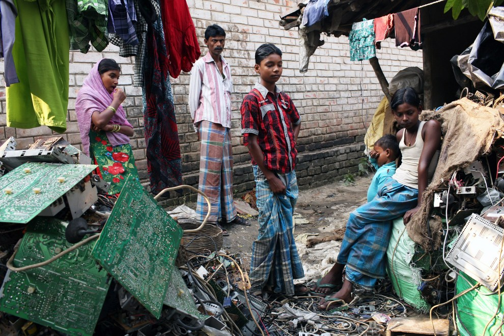 Villagers stand amongst piles of E-Waste in the village of Sangrampur, located south of Kolkata in north-east India. Globally, it is estimated that approximately 50 million tonnes of eWaste are produced annually which much of it ending up in countries such as India.