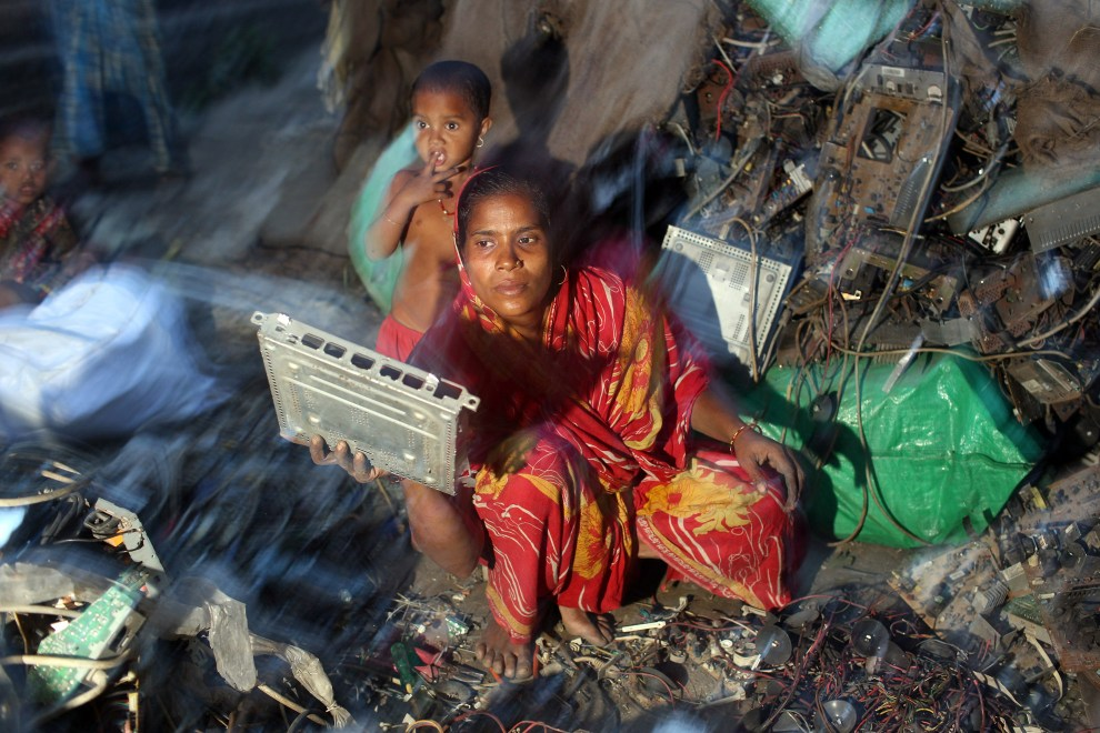 A woman segregates E-Waste as her child stands nearby in the village of Sangrampur, near Kolkata in north-east India.