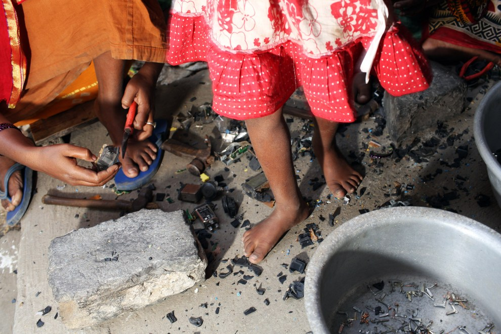 A young girl walls barefoot over E-Waste which her family is breaking down for recycling in the village of Sangrampur. Lead, mercury, arsenic and other toxic elements are released in the breakdown process and people often have little to no safety equipment to protect themselves.