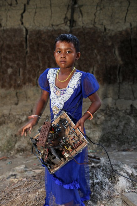 In the village of Sangrampur near Kolkata, a young girl carries a circuit board which she will deliver to her family nearby who are recycling E-Waste. Lead, mercury, arsenic and other toxic elements are released in the breakdown process and those who handle the waste have little to protect themselves from the harmful materials.