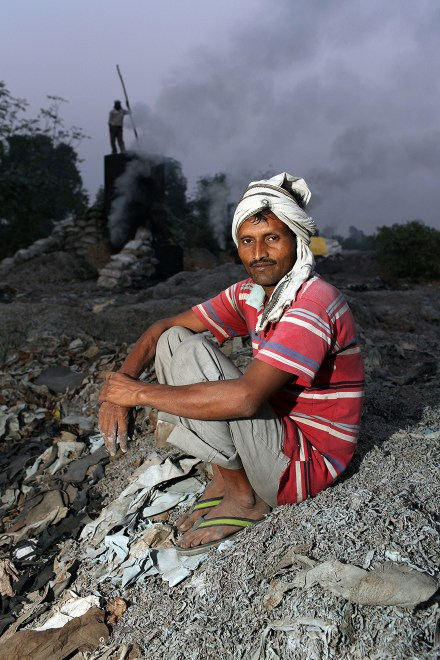 A man sits near a vat used for burning leather trimmings on the outskirts of the town of Kanpur. The leather is burnt, dried and then used as fertiliser and chicken feed.