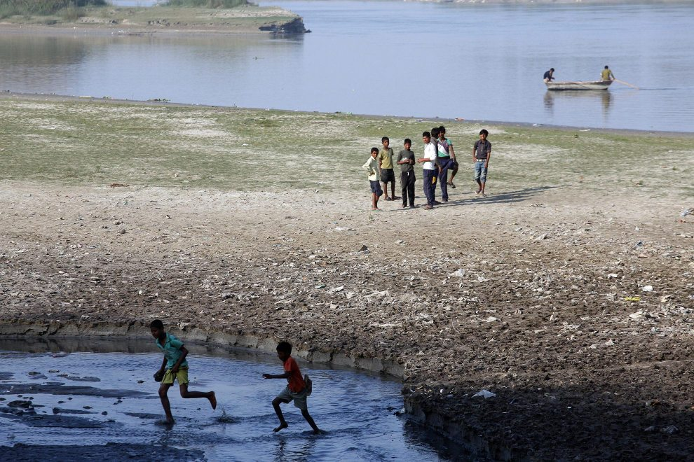 Children running through a polluted tributary of the Ganges River at Kanpur.