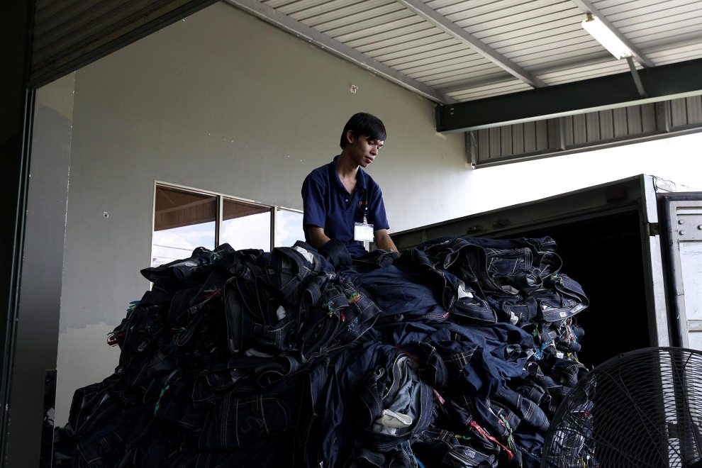 A worker sits on top of a huge pile of jeans that are about to be transported at denim detailing company, Sai-Tex, located outside of Ho Chi Minh City.