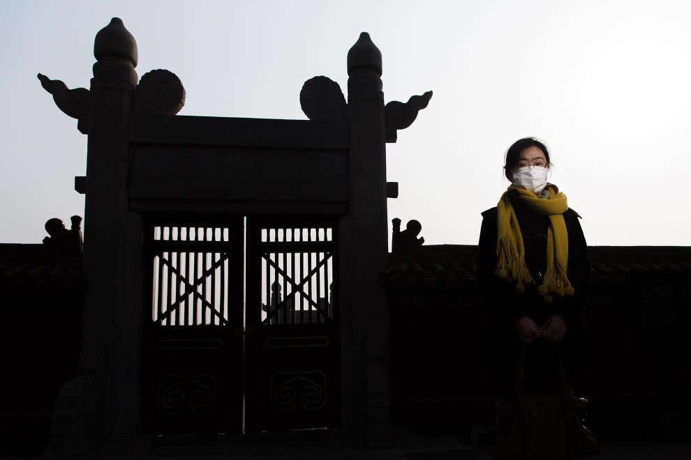 """Miss Song (30), from Dongbei Province, stands near an ornate gate in Beijing's Ditan Park. """"It's very dirty here. I started using the mask last year. From the year before last, China started to get this pollution. Pollution was a very new word for me. At that time, we started to know more about """"2.5"""". My family don't wear masks. I suggested they use them but they didn't do it."""" - PM2.5 reading - 365 - Hazardous"""