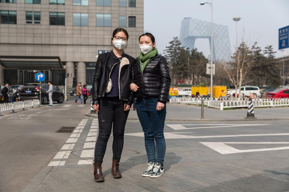 """Ms. Pan (left) and Ms. Zhu (right) are co-workers in an Environmental Landscape Design company in Beijing. """"The weather is too bad""""' explains Ms. Pan. """"It's really uncomfortable. I can already feel the cough and headaches. In my professional area, we discuss [this issue] a lot. The air is getting worse and worse."""" PM2.5 reading - 196 - Unhealthy"""