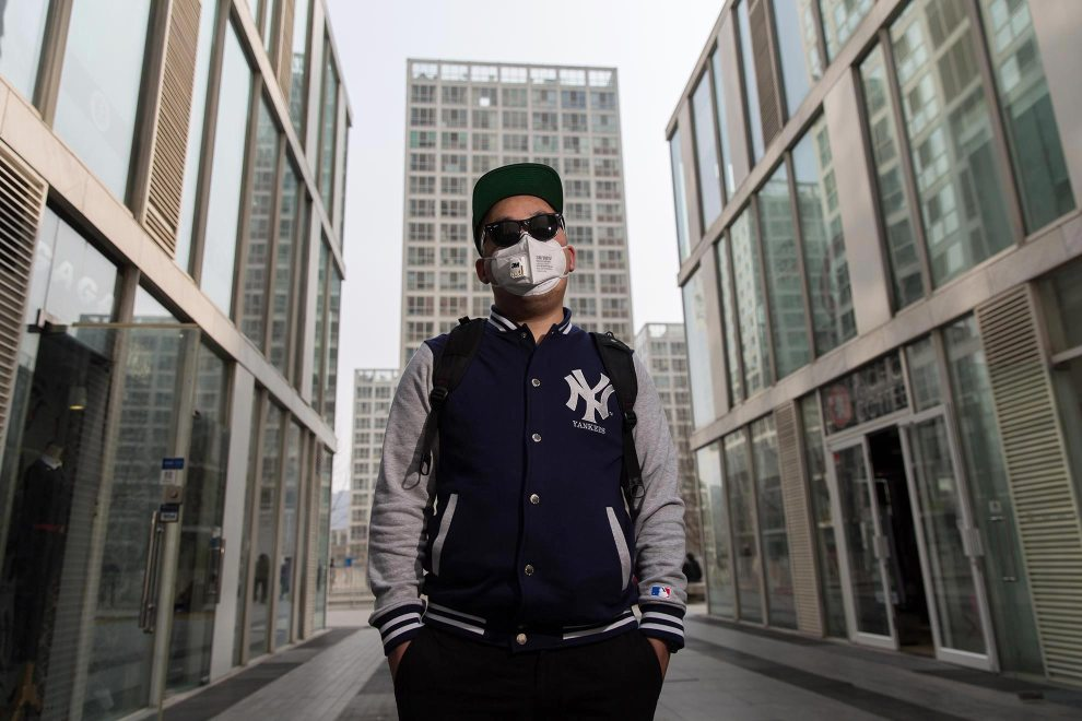 """Ren (27), a student and Beijing resident, stands in the cities modern CBD area. """"I started using the mask last year when the pollution got bad. I didn't pay much attention before that"""", he explains. """"I don't like wearing it but I have to. I watched the [Chai Jing] documentary many times. I shared it with everyone. Now, I pay attention to our behaviour. The documentary inspired me. The future? It's hard to get the environment back. I'm thinking about emigrating."""" PM2.5 reading - 184 - Unhealthy"""