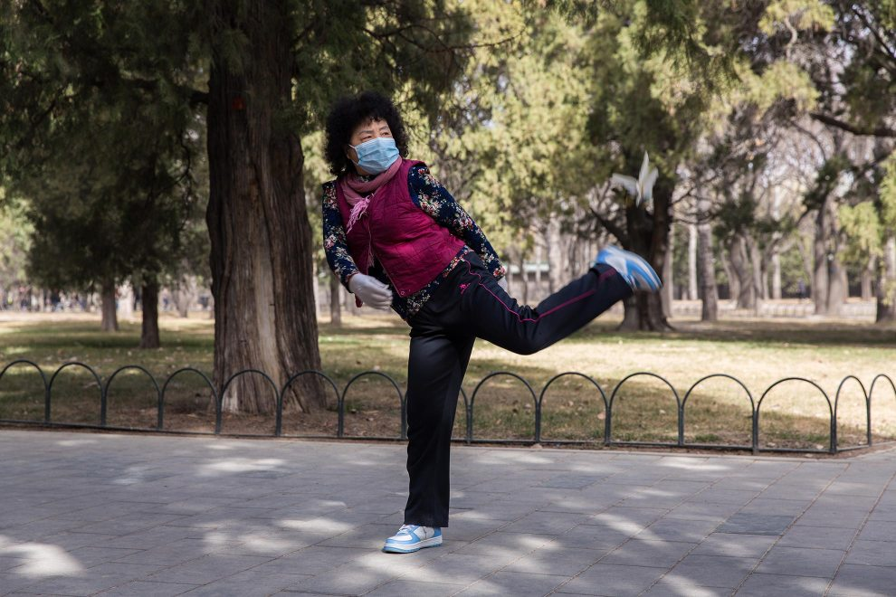 In Beijing's TianTan Park, a woman plays with a Jianzi, a traditional Chinese game which requires the participants to keep it in the air by kicking. PM2.5 reading - 89 - Moderate