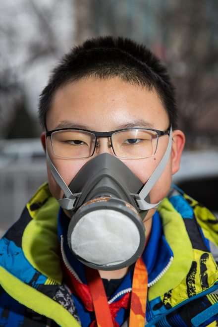 """Qi (name changed), a 13-year old middle school student, wears an advanced air filtration mask in central Beijing. """"I'm more concerned about the pollution than my parents. Since 2012, my parents told me to stay inside more. I asked my parents to buy this for me. My classmates think I'm strange."""" PM2.5 reading - 188 - Unhealthy"""