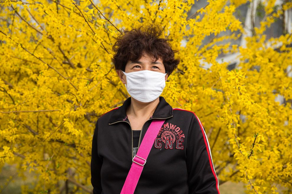 """A tourist (name withheld) from Heilongjiang province, in north-west China, visits the Olympic green in central Beijing. """"I knew from TV that the air quality is bad in Beijing, so I bought it before I came here"""", she says. """" In Heilongjiang, the air is better than here but in the [city] downtown area it's similar"""". PM2.5 reading - 218 - Very Unhealthy"""