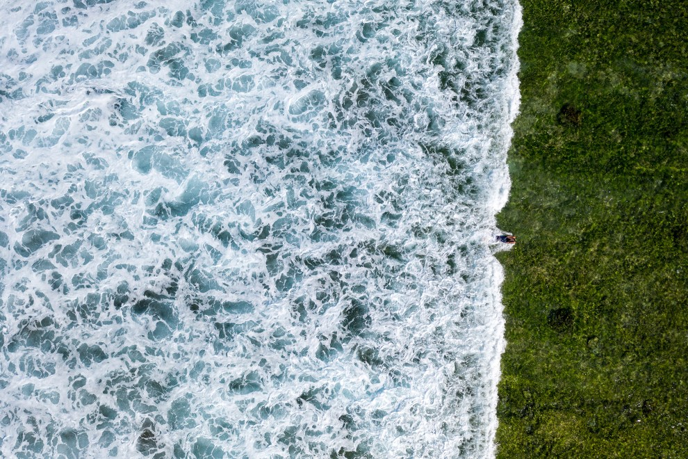 A boy is seen from above as he rides a wave that is travelling in from the Pacific Ocean onto the Tuvaluan coastline.