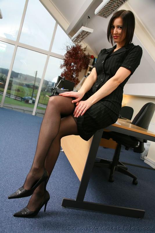 tres jolie secretaire brune en tailleur porte jarretelles bas noirs et escarpins noirs attendant le prince charmant au bureau