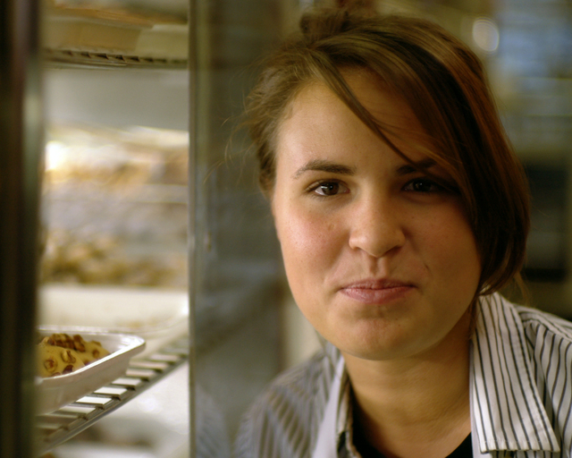 September 17, 2009. Philadelphia, Pennsylvania. Swiss Bakery worker Katie kneeling next to a pastry case after filling all the trays with butter cookies.