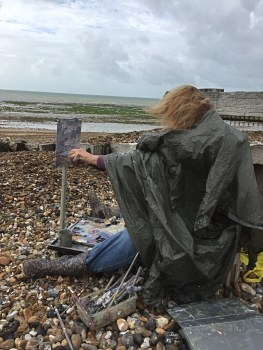 Frances painting in the wind and rain at Climping Beach