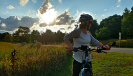 Hometown Bicycles cyclist looking back at a beautiful Island Lake sunset