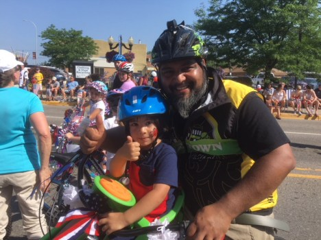 Hometown Bicycles' Shaun Bhajan with son Liam riding in the 2018 Brighton Fourth of July Parade