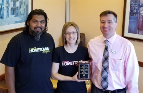 Shaun and Dawn Bhajan of Hometown Bicycles accepting an award from Brighton Optimist Club's President-Elect, Gary London