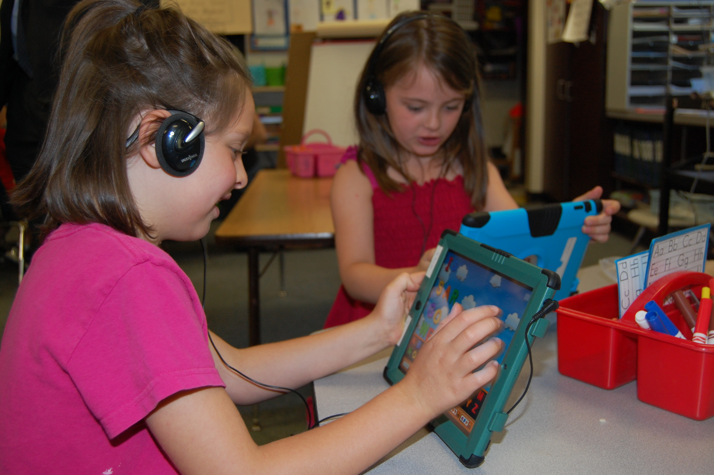 Sara Richard, left, and Lauren Fletcher, right, use their iPads in their classroom and Fairview Elementary School to learn letters and to spell words.