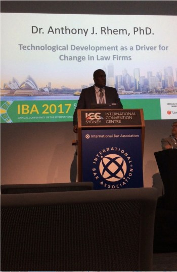 Dr. Anthony Rhem speaking at the podium at the IBA Conference