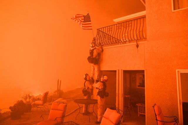 Firefighters remove a U.S. flag as flames from the