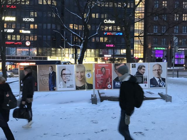People walk by campaign posters in downtown Helsinki.