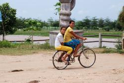 Two girls cycling past