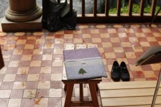 温かみのあるマットを中心に、雨で濡れたタイルの背景、無造作に置かれ傘と靴の黒など、その日の記憶を思い起こさせるモチーフが随所に散りばめられています。