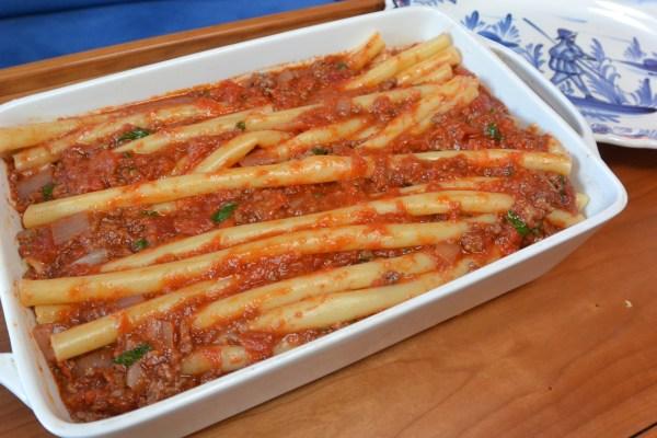 adding sauce to pastitsio