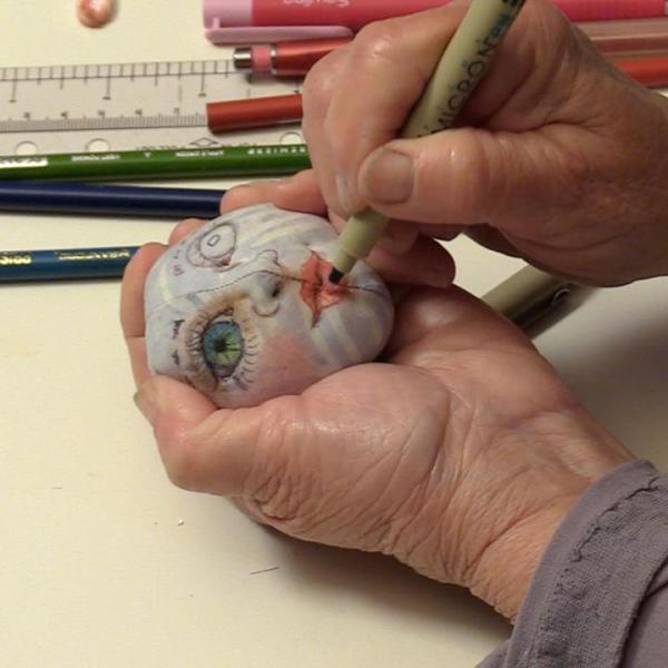 Image of drawing a face on a cloth doll head — from Cloth Doll Mermaids featuring Patti Medaris Culea