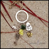 "JADED - Silver-plated circle with 6 dangling charms. Pewter elephant and key, tiny clear glass beads, lemon jade chips, green jade disc, and pewter and brass reversible word charm. 24"" silver plated link chain. $45 as shown."