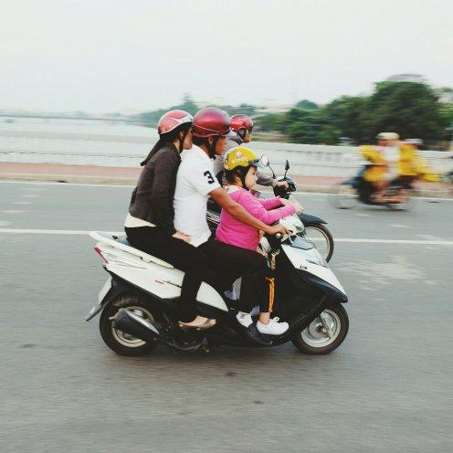 Kleine Familie auf dem Moped